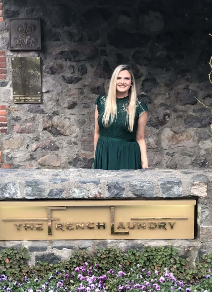 Chandice Probst standing by the rock wall and The French Laundry sign in a green dress.