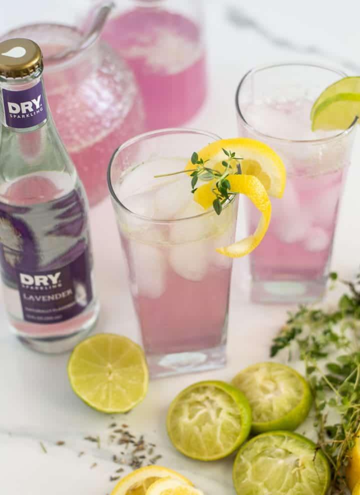 Glasses filled with lavender lemonade and lemon zest