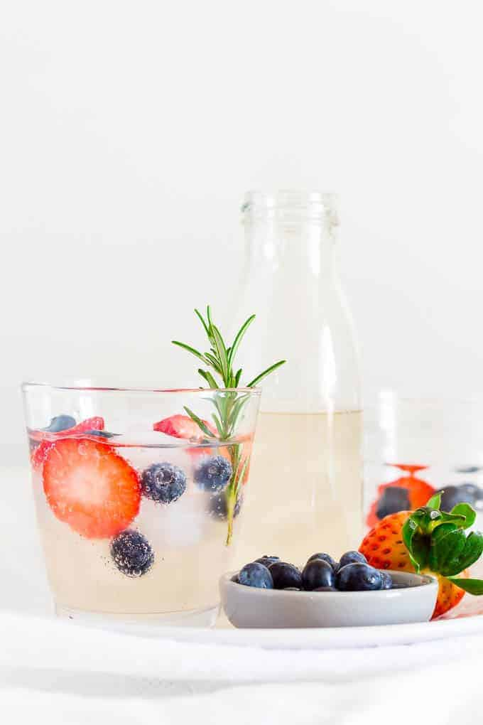 Tall pitcher and glass of ginger beer mocktail with berries