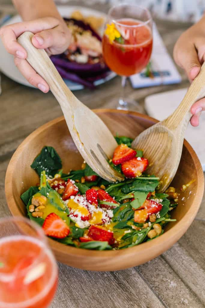 Salad being tossed with wood utensils
