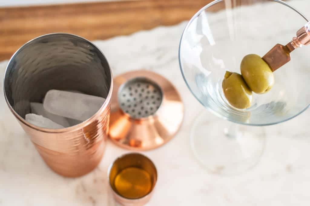 Tumbler with ice and martini glass with green olives