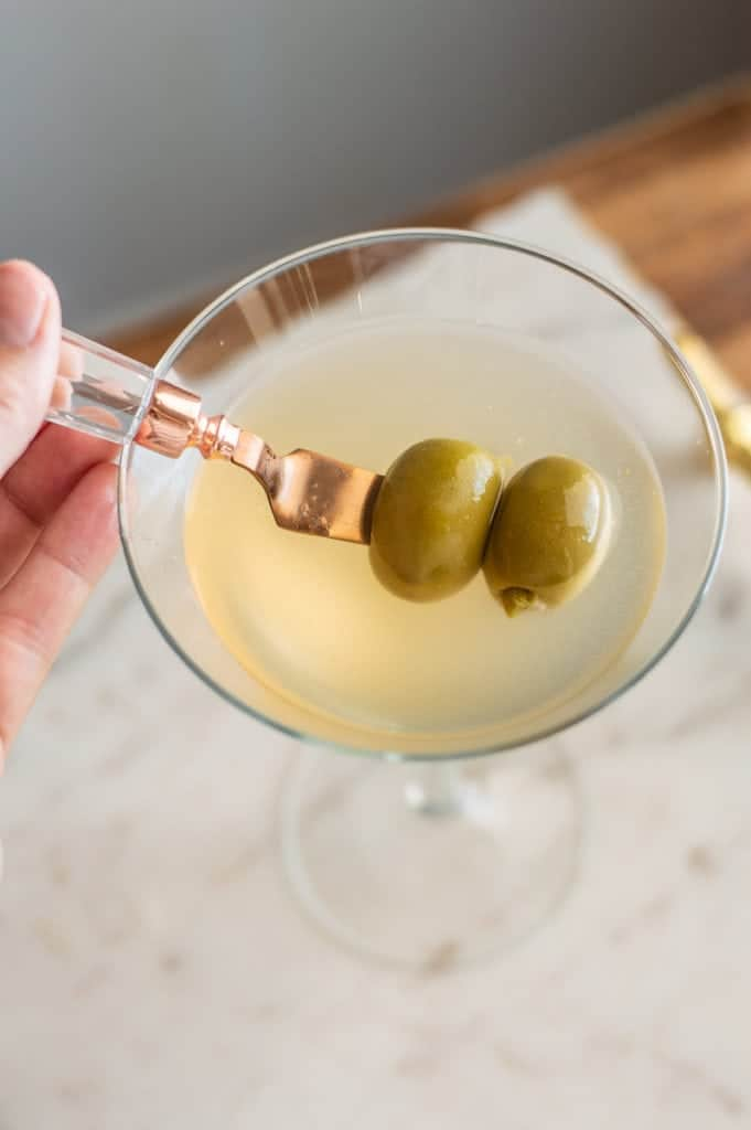 Non-alcoholic vodka dirty martini overhead shot with two green olives
