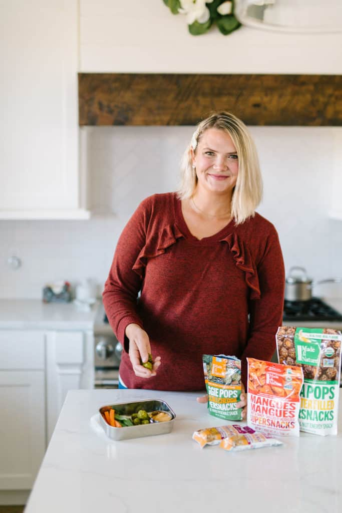 Mom with easy snacks and dried fruit in white kitchen