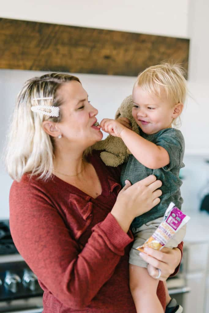 Mom smiling while toddler feeds her