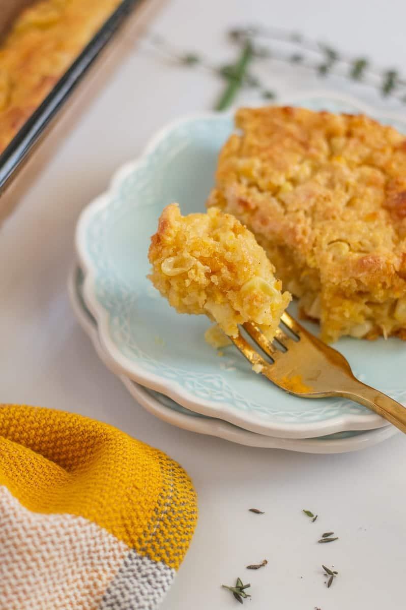 Gluten-free cornbread casserole on a blue plate with gold fork