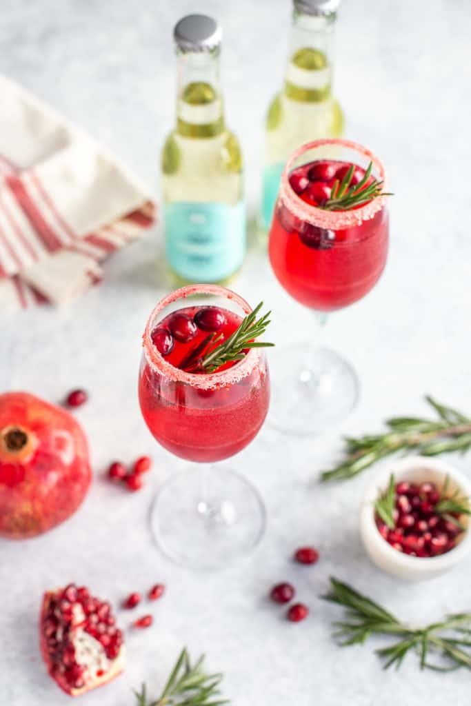 Prosecco drink in glasses with cranberries, pomegranate and rosemary