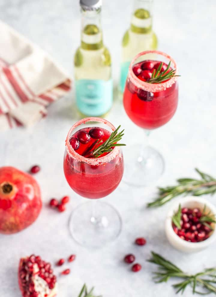 Prosecco drink with cranberries and rosemary in a glass flute