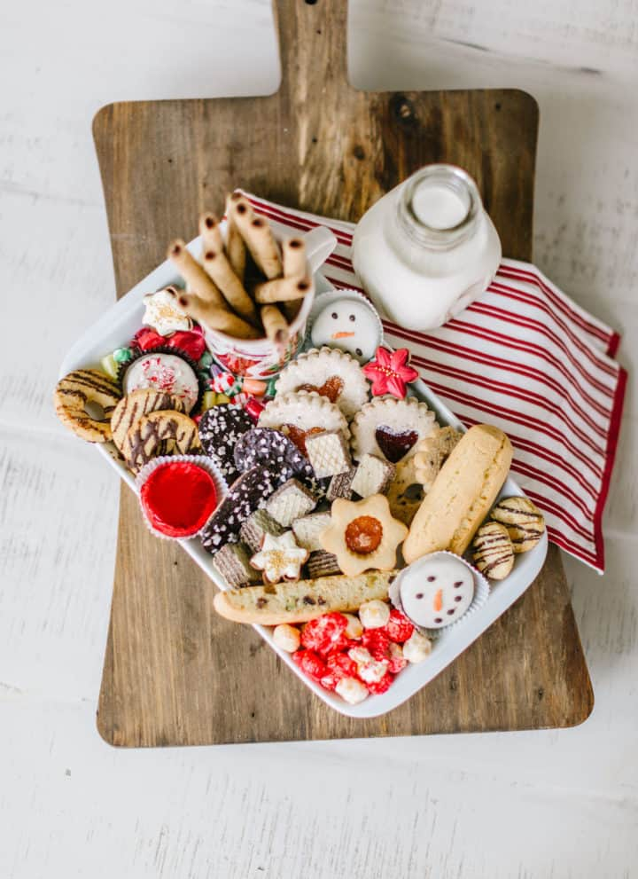 Christmas cookies on a platter with towel and milk