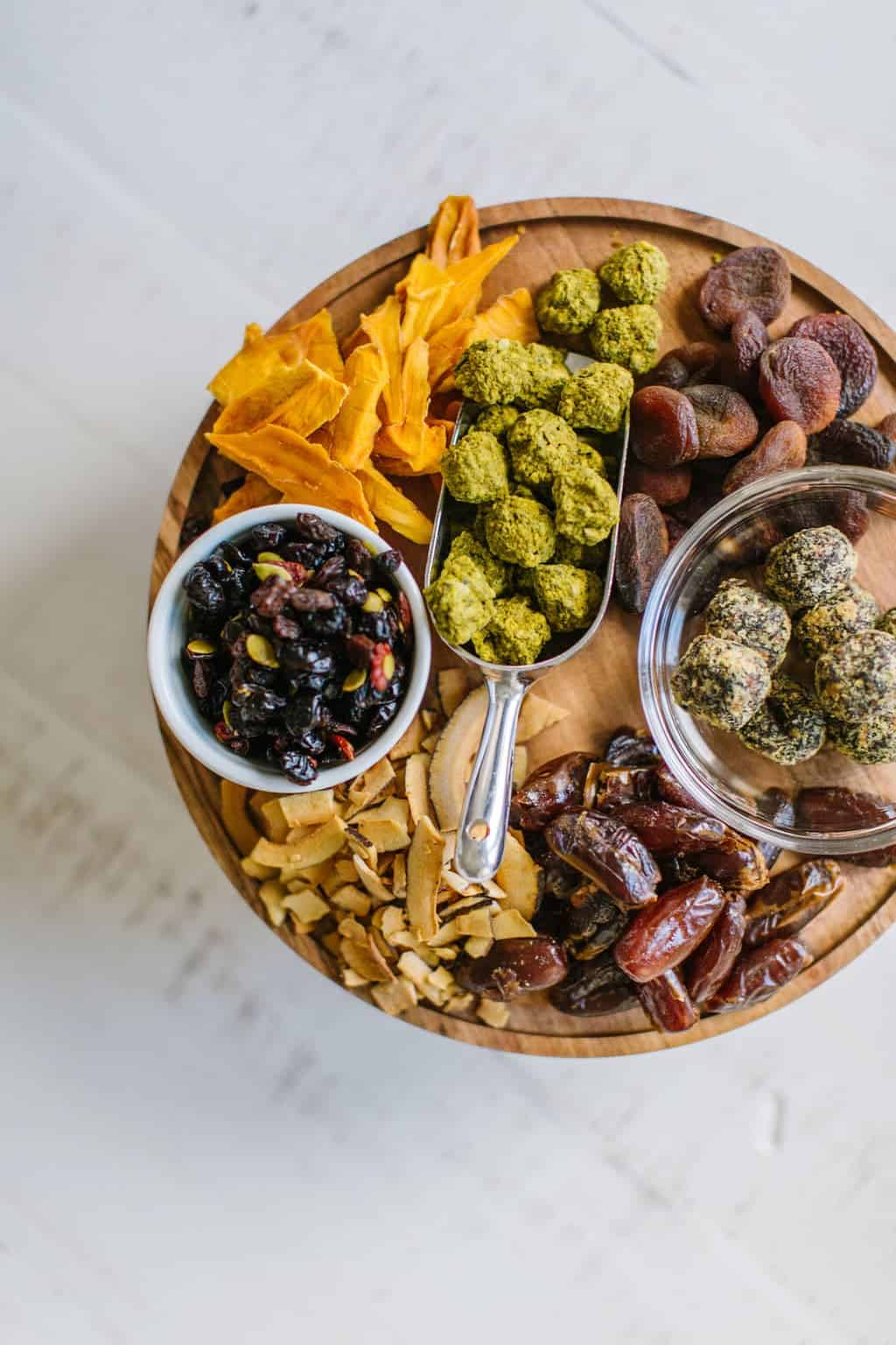 Round wood board with dried fruit, coconut chips and healthy snacks