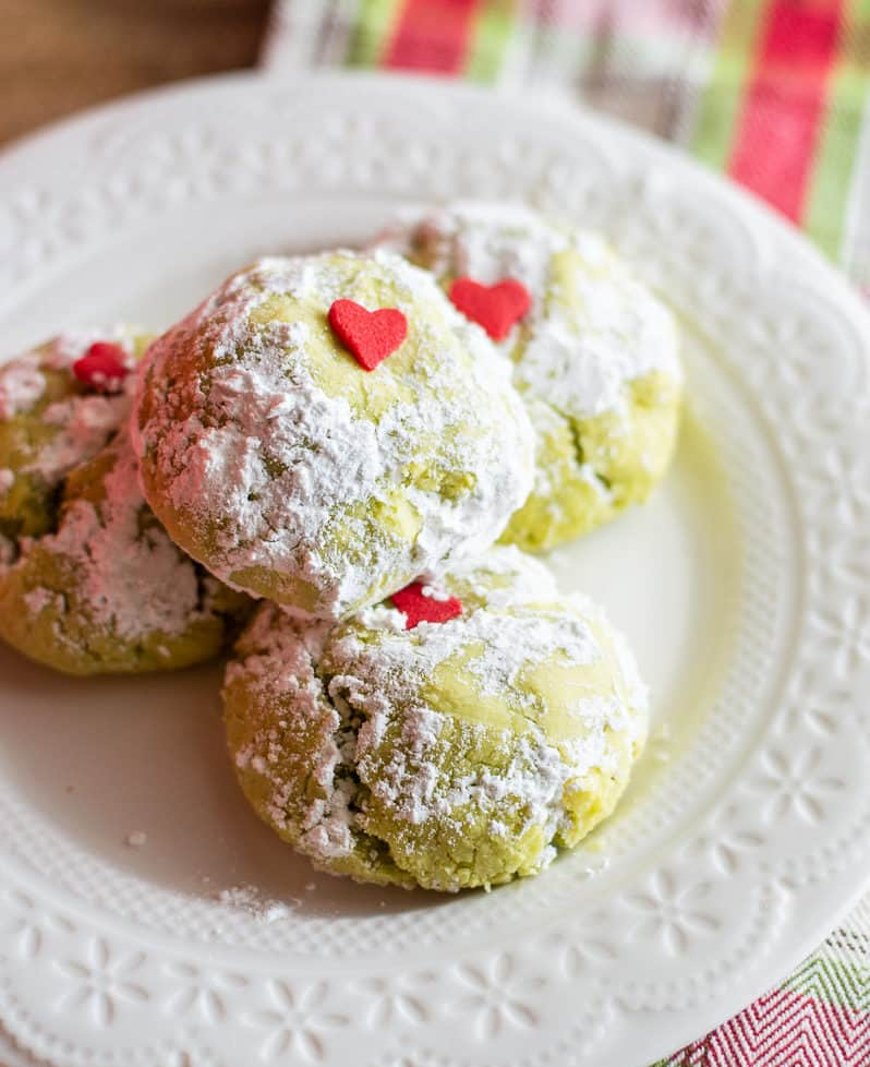 Grinch cookies on a white plate with holiday towel