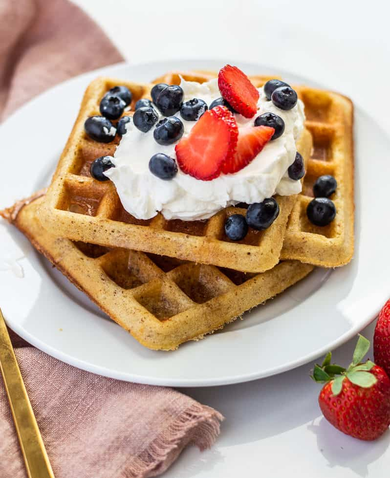 Three square waffles on a white plate with berries