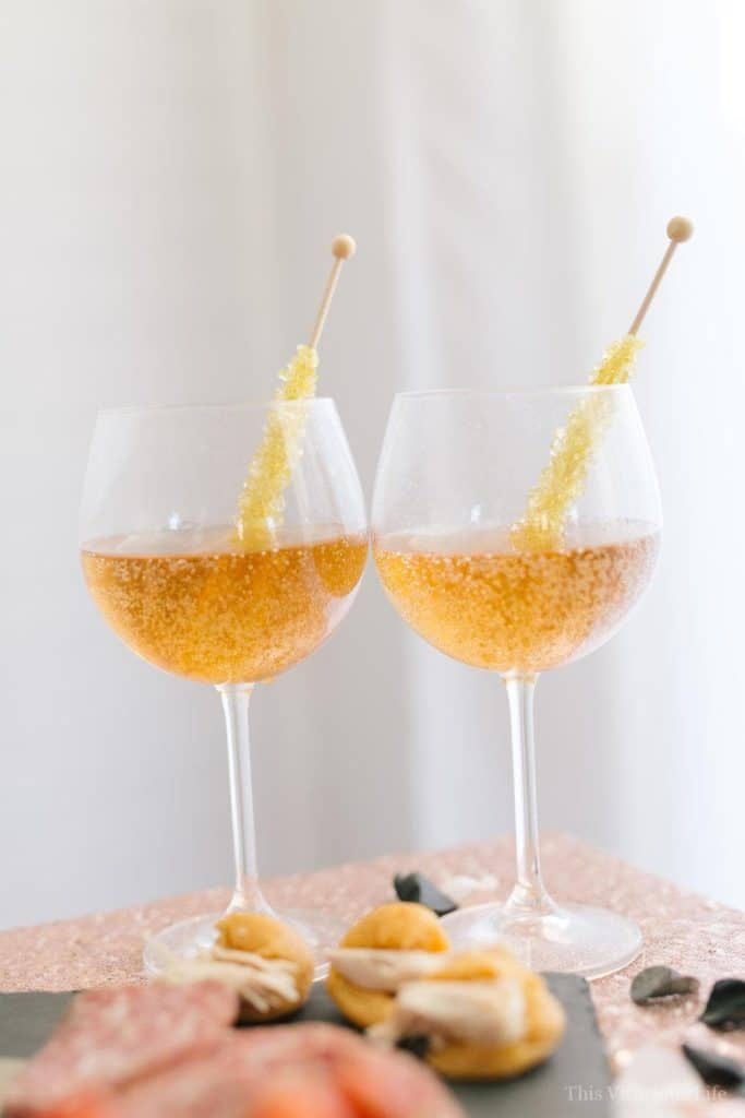 Sparkling cider in wine glasses with rock candy suckers