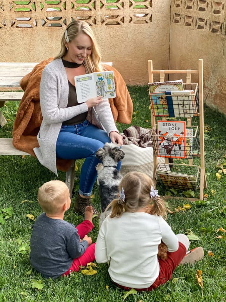 Lady reading books outside to two kids