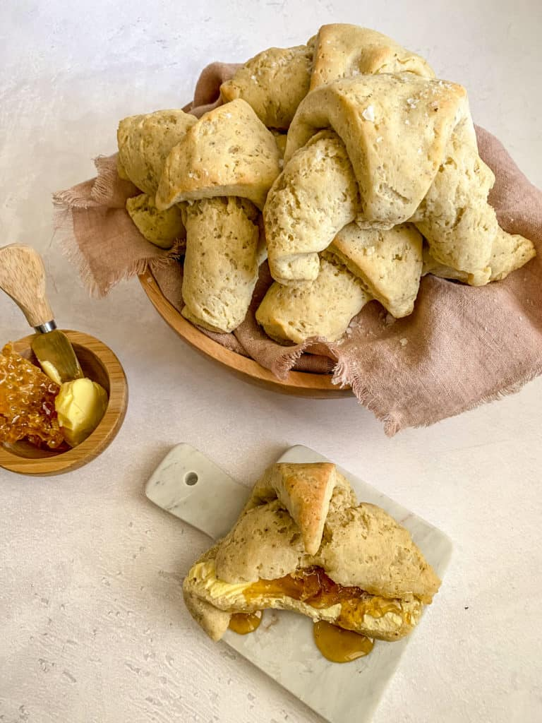 gluten-free sourdough crescent rolls in a bowl and on a little tray