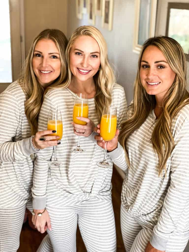 Three gals with orange juice in glasses