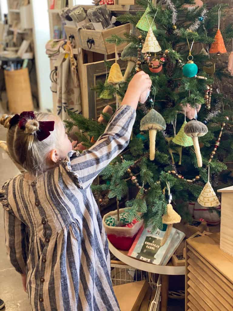 Little girl decorating modern Christmas tree
