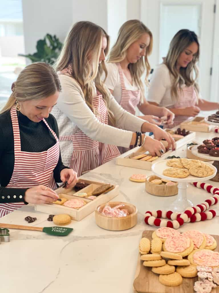 Girls in kitchen making holiday cookie boxes