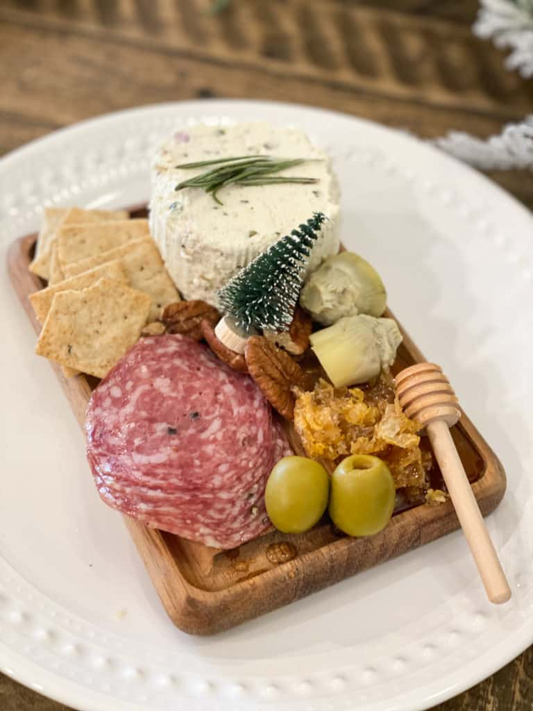 Individual charcuterie board on a wood slab on a white plate