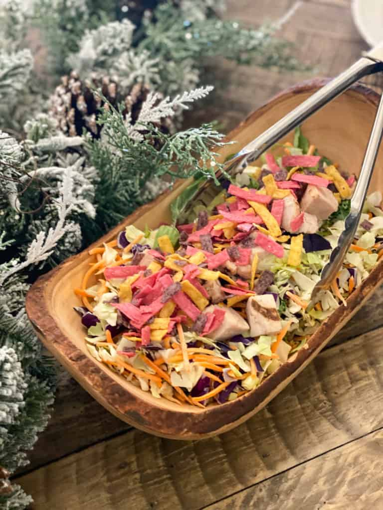 Salad with tortilla strips multicolored in a wood bowl