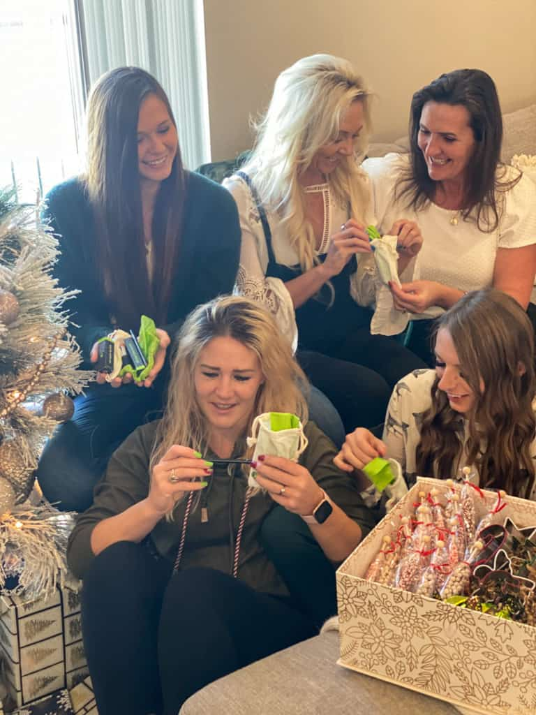 Five ladies smiling opening gifts
