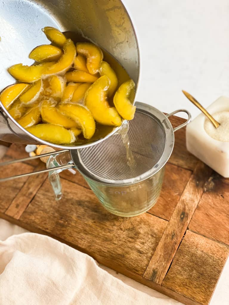 Peach Simple Syrup being poured into a strainer
