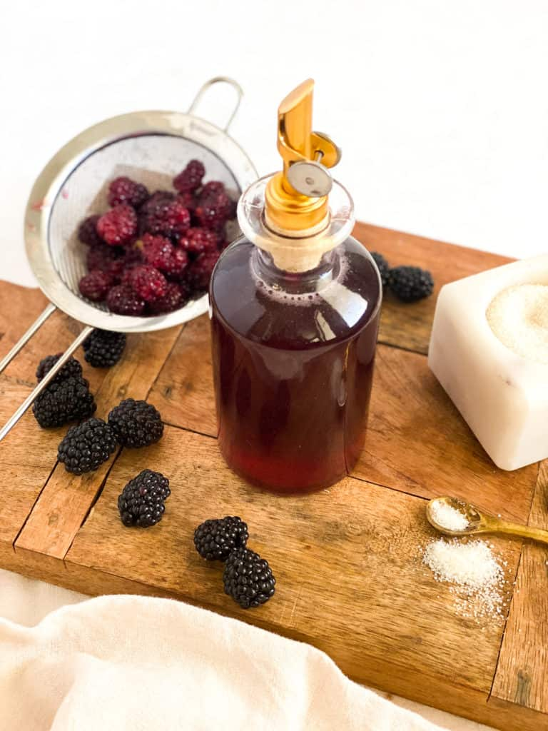 Blackberry Simple Syrup in a glass bottle with berries around