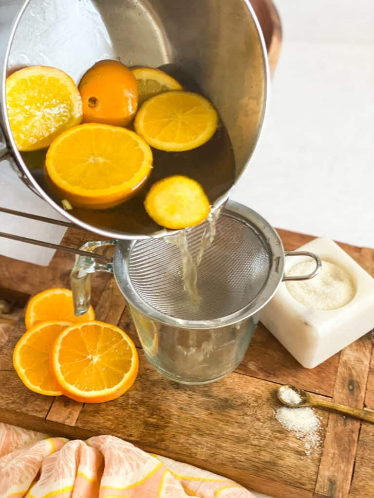 Orange Simple Syrup being poured into a strainer