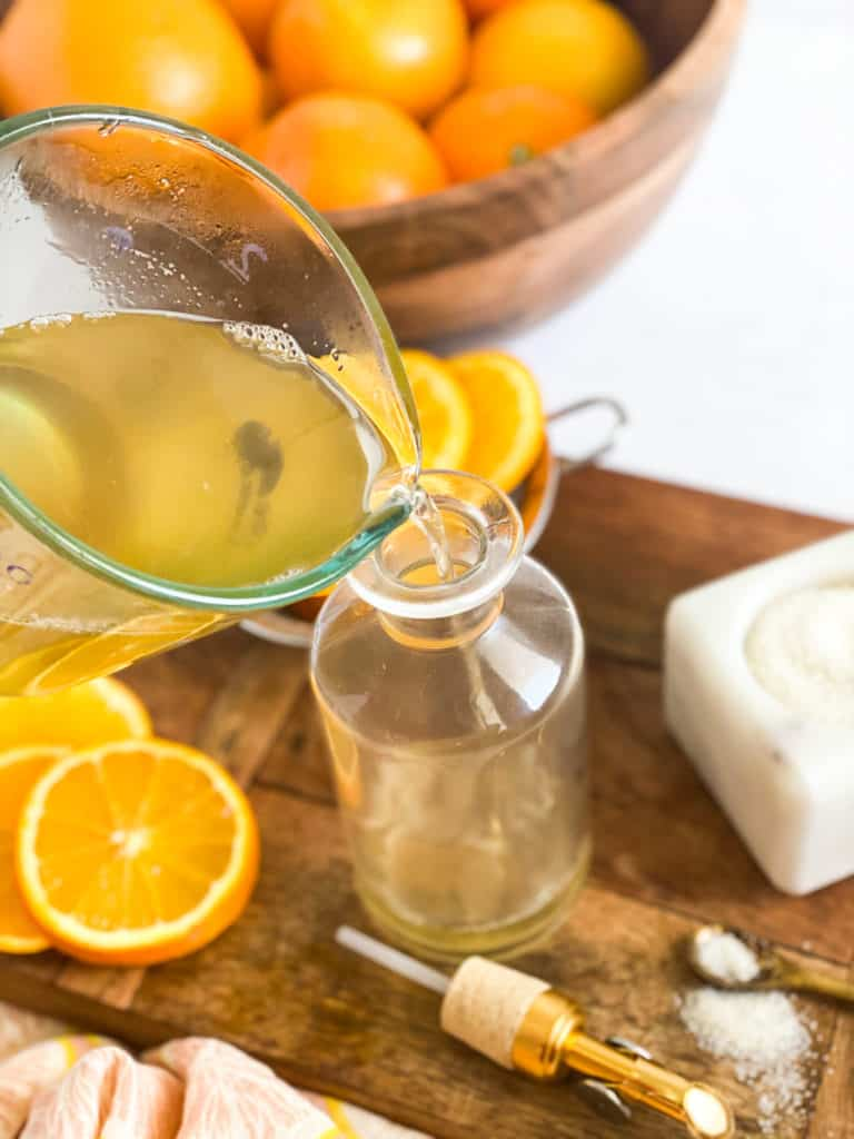 Orange Simple Syrup being poured into a glass