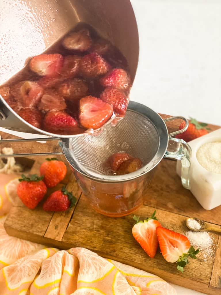 Strawberry Simple Syrup being poured into a strainer