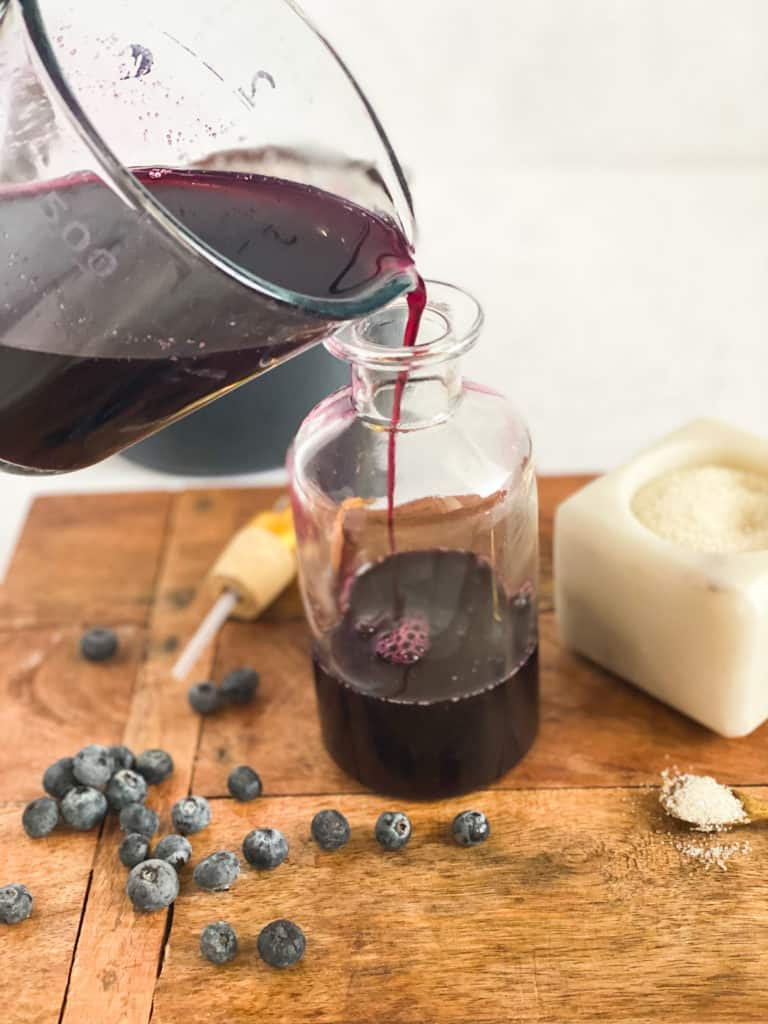 Blueberry Simple Syrup being poured into a glass jar