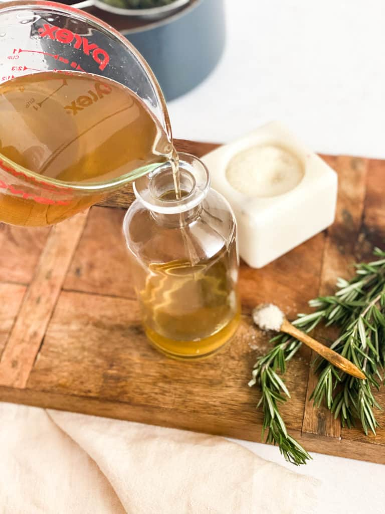 Rosemary Simple Syrup being poured into a glass jar