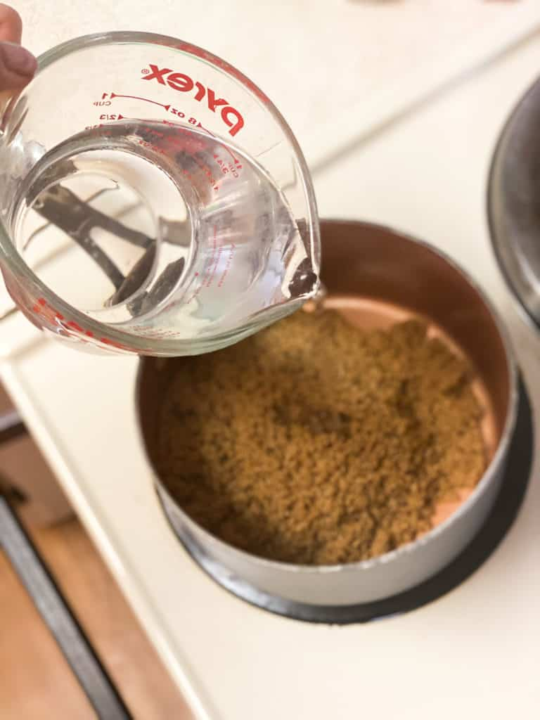 Water being poured into a saucepan with brown sugar