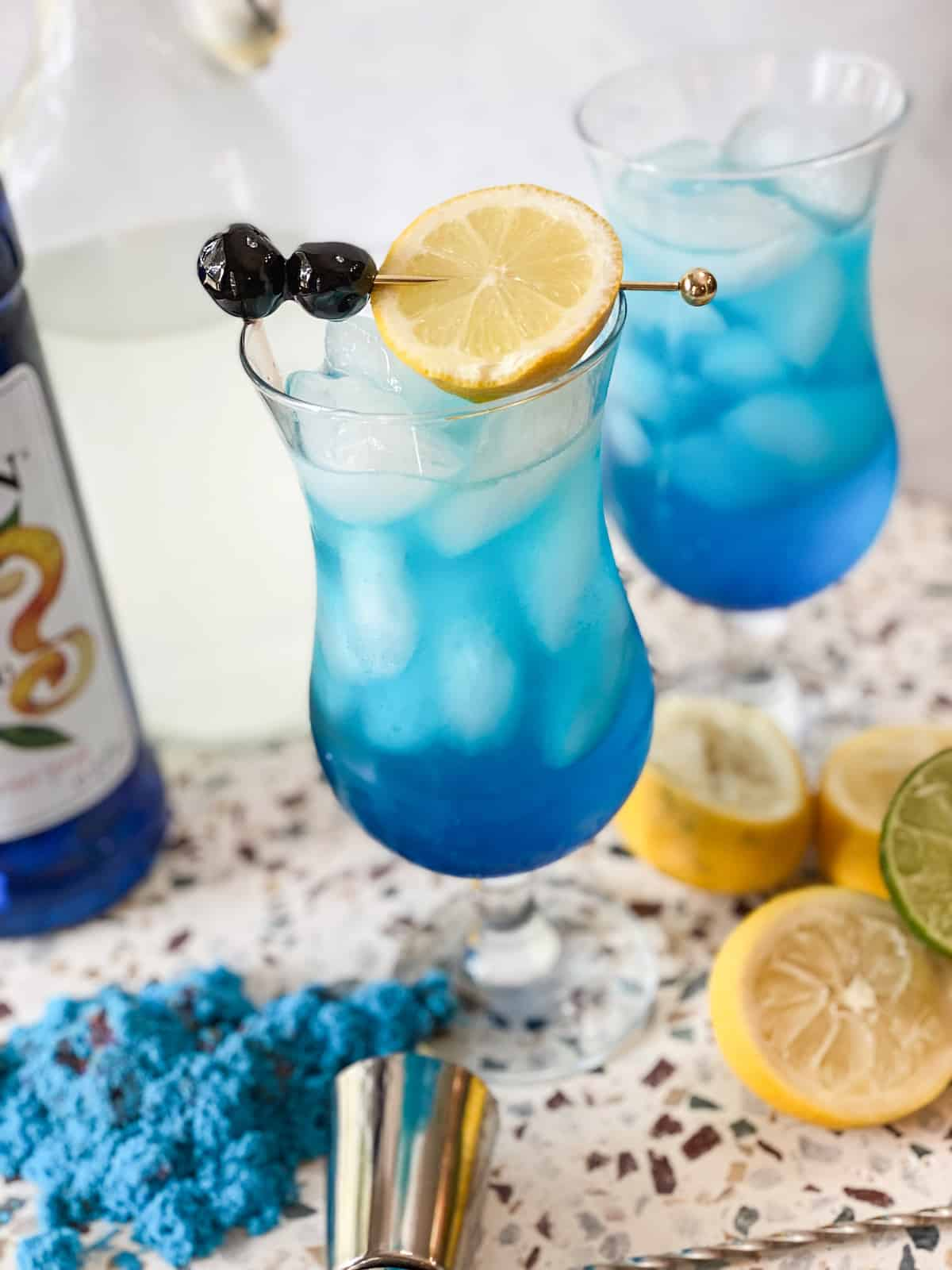 Blue lagoon mocktail in a hurricane glass with lemon and cherries