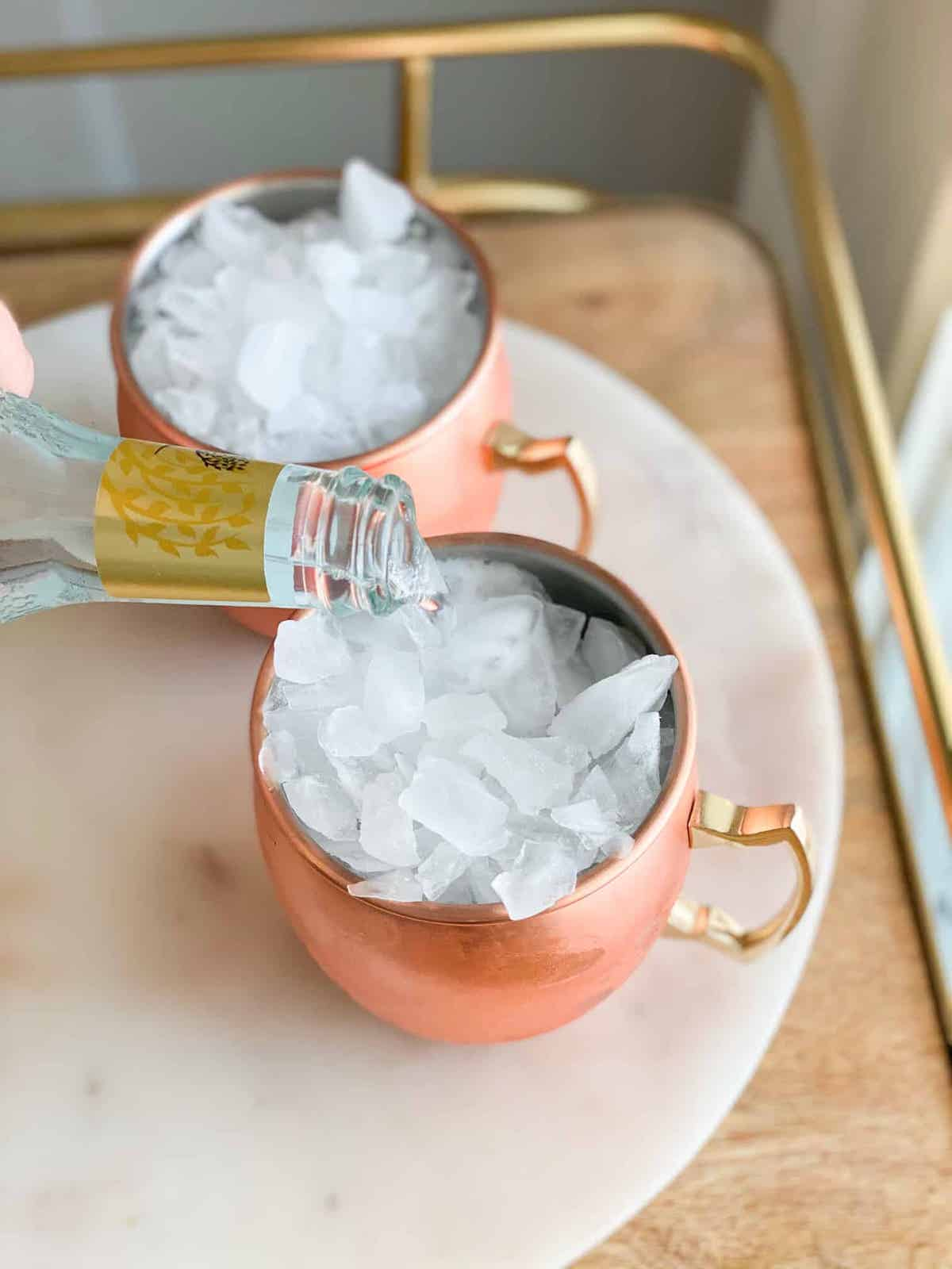Ice in a copper cup with ginger beer being poured into a cup